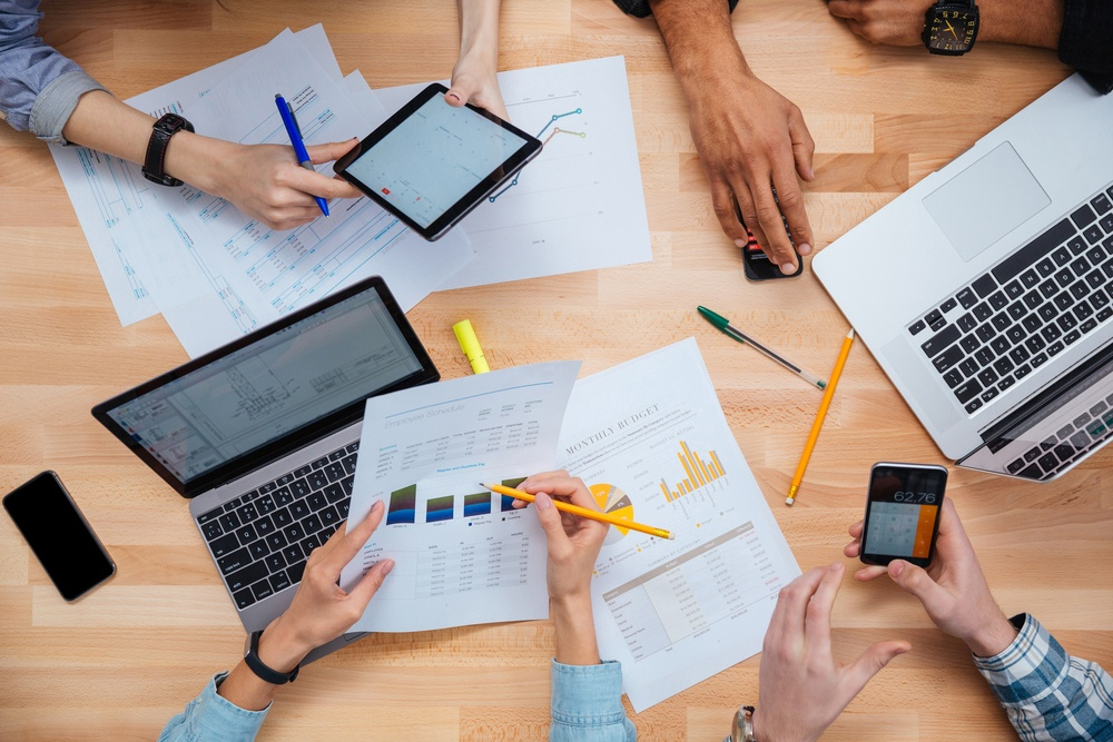 Group of people working with laptops, tablet and smartphones together and making financial report.jpeg